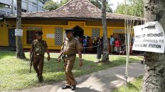Sri Lankans queue to cast their votes as police officers patrol at a polling station during the presidential election in Colombo, Sri Lanka, Saturday, Nov. 16, 2019. Polls opened in Sri Lanka's presidential election Saturday after weeks of campaigning that largely focused on national security and religious extremism in the backdrop of the deadly Islamic State-inspired suicide bomb attacks on Easter Sunday. (AP Photo/Eranga Jayawardena)
