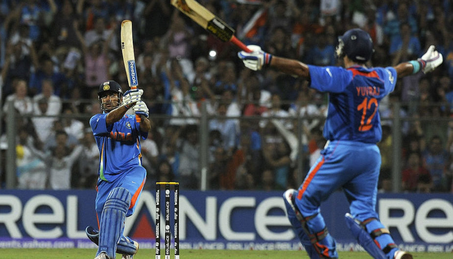 Indian captain Mahendra Singh Dhoni (L) hits a six to win against Sri Lanka as teammate Yuvraj Singh reacts during the Cricket World Cup 2011 final at The Wankhede Stadium in Mumbai on April 2, 2011. India beat Sri Lanka by six wickets. AFP PHOTO/Indranil MUKHERJEE (Photo credit should read INDRANIL MUKHERJEE/AFP/Getty Images)