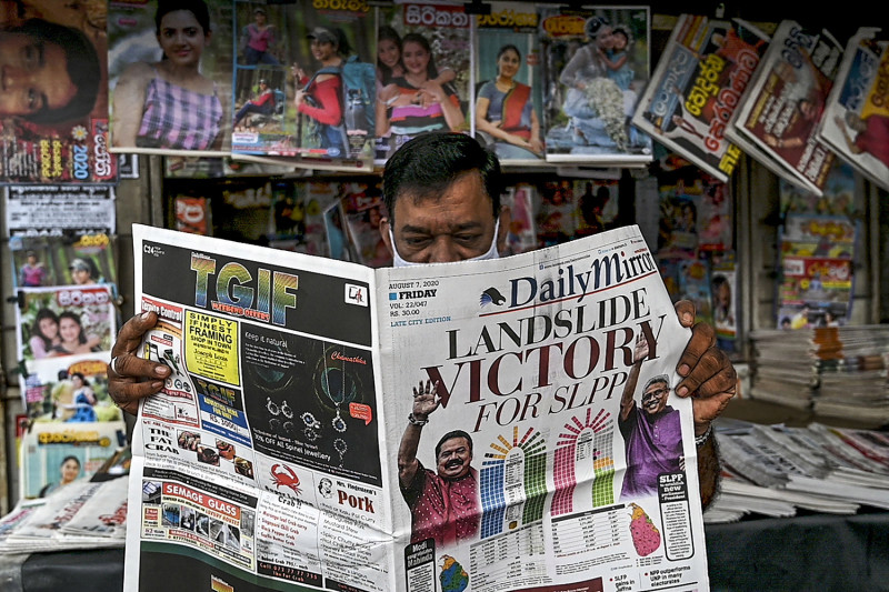 A man reads a local newspaper covering the results of Sri Lanka's parliamentary elections in Colombo on August 7, 2020. - Sri Lanka's ruling Rajapaksa brothers have secured a two-thirds majority in parliamentary elections, giving them powers to change the constitution and unravel democratic safeguards, final results showed on August 7. (Photo by ISHARA S. KODIKARA / AFP) (Photo by ISHARA S. KODIKARA/AFP via Getty Images)