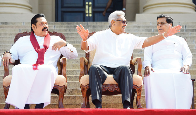 Sri Lanka's new President Gotabaya Rajapaksa (C) and his Prime Minister brother Mahinda Rajapaksa (L), sit for a group photograph after the ministerial swearing-in ceremony in Colombo on November 22, 2019. Sri Lanka's new president announced holding parliamentary elections six months ahead of schedule after giving key portfolios of finance to his prime minister brother Mahinda Rajapaksa. / AFP / ISHARA S. KODIKARA